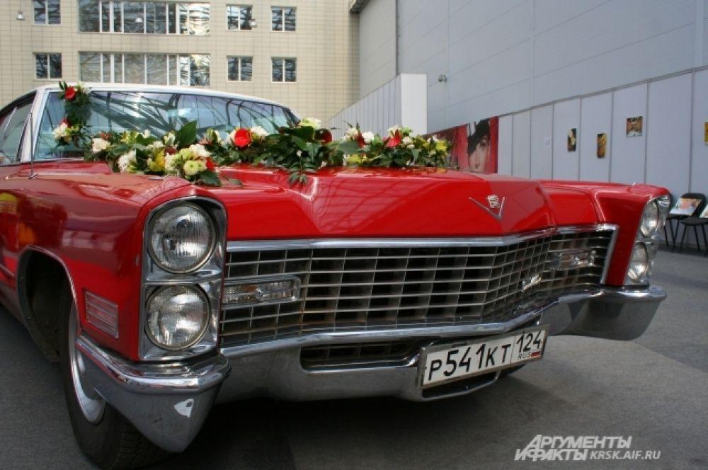 Экспонат свадебной выставки - Cadillac. Украшен цветами и выглядит празднично.