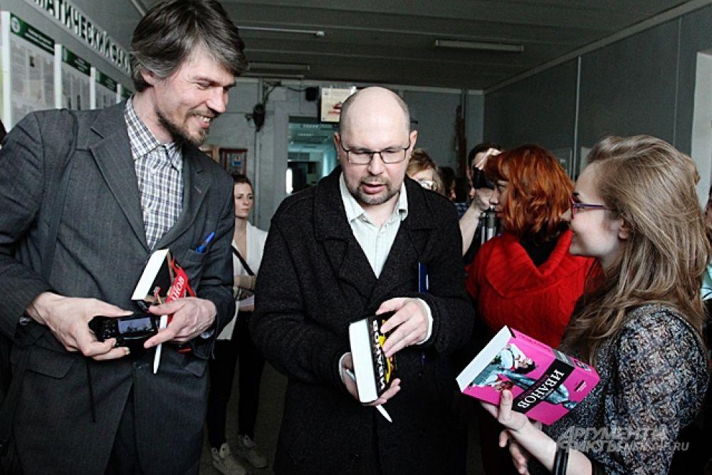 Писатель Иванов раздает автографы тем, кто пришел написать диктант в НГУ.