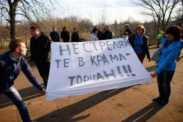 Они держали в руках плакаты, в то время как на территории аэропорта оставались несколько десятков военных из различных подразделений.