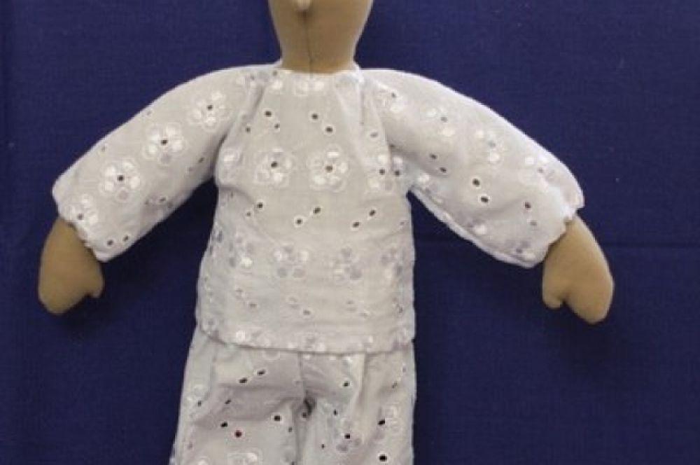 Одеваем нашу куклу. Возле горловины и рукава прошиваем и стягиваем. Штанишки закрепляем прямо на туловище куклы.