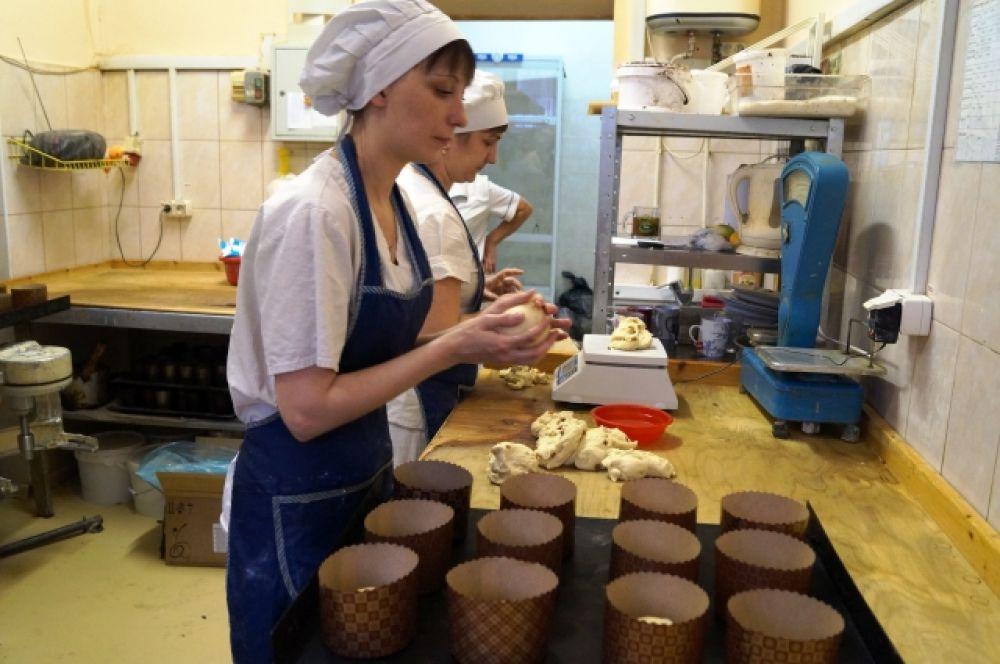 Пекарь заполняет формочки