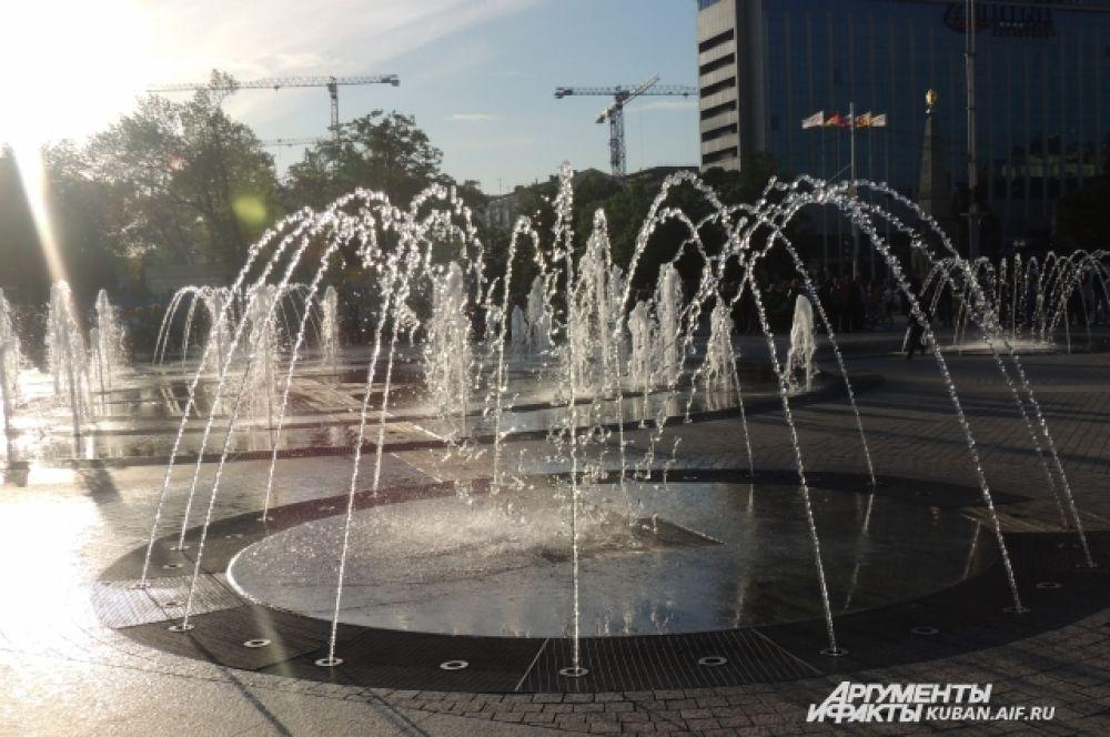 Струи фонтана играют на закатном солнце.