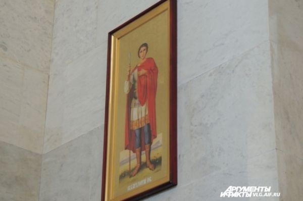 А на стенах иконы почитаемых русских святых.