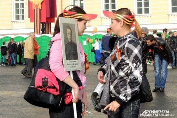 Пришедшим раздавали кепки с изображением Георгиевской ленты.