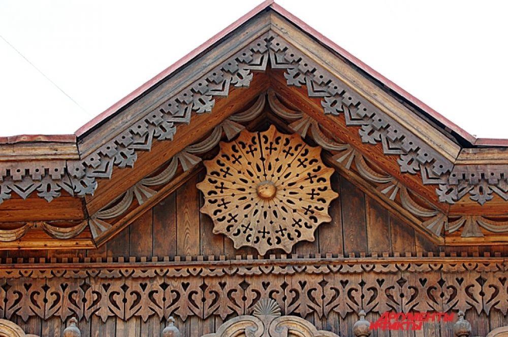Наличники окон украшены накладной пропильной резьбой растительного орнамента с полубалясинами на боковинах.