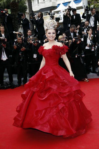 Российская светская львица Лена Ленина пошла ещё дальше, выбрав дерзкого красного цвета пышное платье. Большое внимание привлёк целый массив украшений, закреплённый у Лены на голове.