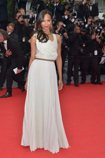 Зои Салдана посетила церемонию открытия в простом белом платье, «усиленном» массивной цепочкой на поясе и сложным узором.