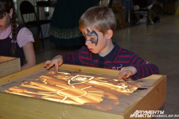 Те, кто ещё не умеет писать, могли порисовать, но не на обычной бумаге. Дети с большим удовольствием учились создавать картины на песке.