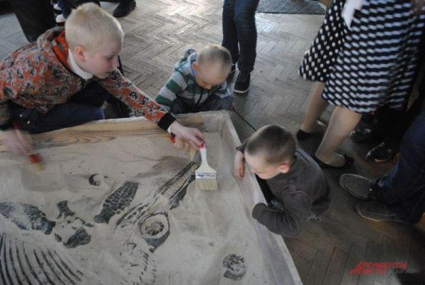 Палеонтологическая песочница – дети извлекают из земли скелет ихтиозавра.