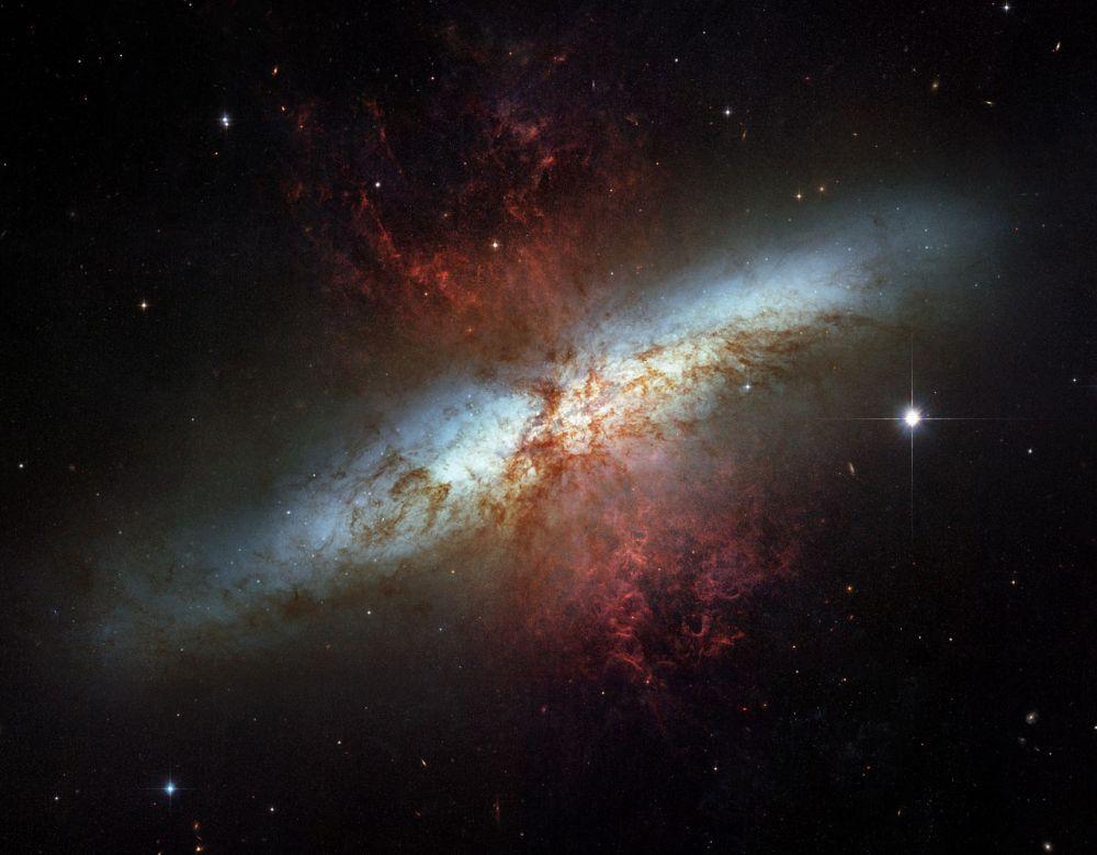Спиральная галактика Сигара с мощным звездообразованием в созвездии Большая Медведица. В центре галактики расположена сверхмассивная чёрная дыра, масса которой превышает массу Солнца в 30 миллионов раз.