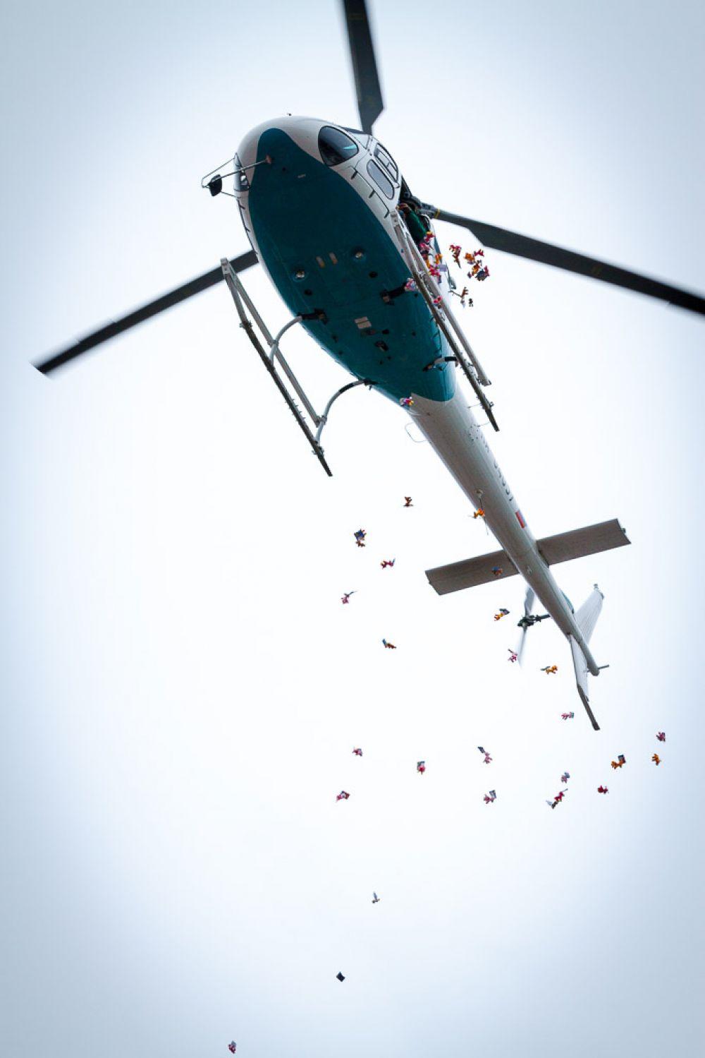 Над площадью появился вертолет, с которого начали сыпаться маленькие игрушки.