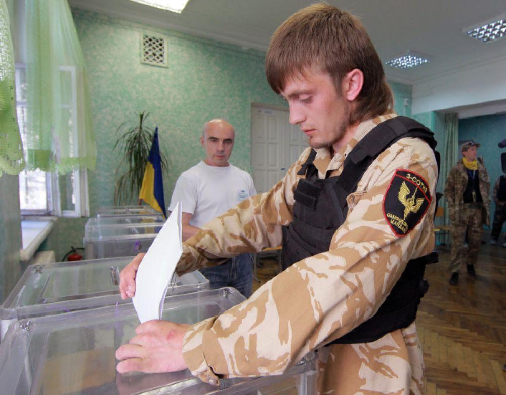 Участник самообороны Майдана голосует на внеочередных выборах президента Украины на одном из киевских избирательных участков.