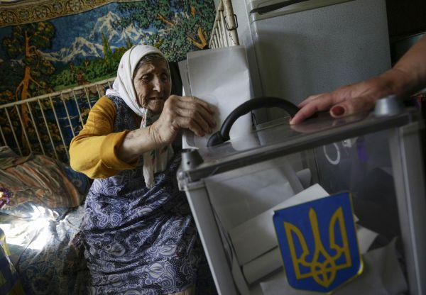 Село Кодра на севере Украины. К пожилой бабушке, не способной прийти на избирательный участок, принесли корзину для голосования домой.