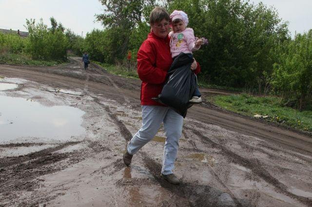 Не все коляски могут проехать по дорогам Потанино, поэтому детей там носят на руках.