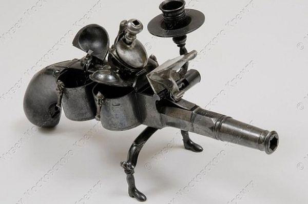 Настольный пистолет-чернильница сделан тульским мастером в 1768 году. Сбоку ячейки для песка и чернил. Подставка для свечи и гусиного пера. Странной формы дуло калибра 9,4 м. Всё сделано из железа, стали. Украшено ковкой, резьбой, гравировкой.