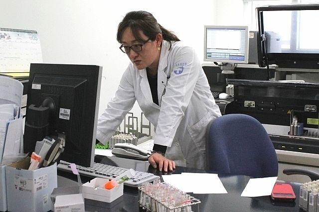 Корейский врач из города Сокчо проверяет анализ крови российского пациента.