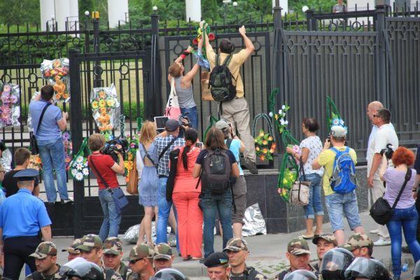 Митингующие пытаются повесить траурные венки на забор генконсульства