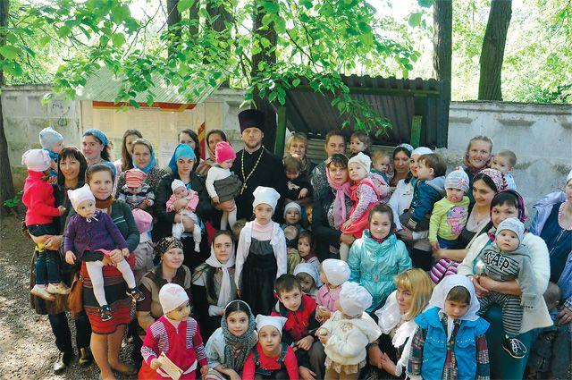 Отец Алексей Пшеничников с матушкой Ольгой, маленькими прихожанами и их родителями.