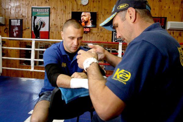 Тренер бинтует руки боксера Макса Бурсака