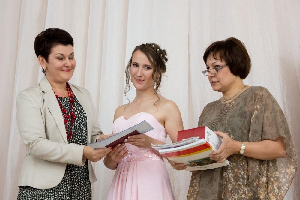 Директор гимназии вручает аттестаты своим выпускницам.