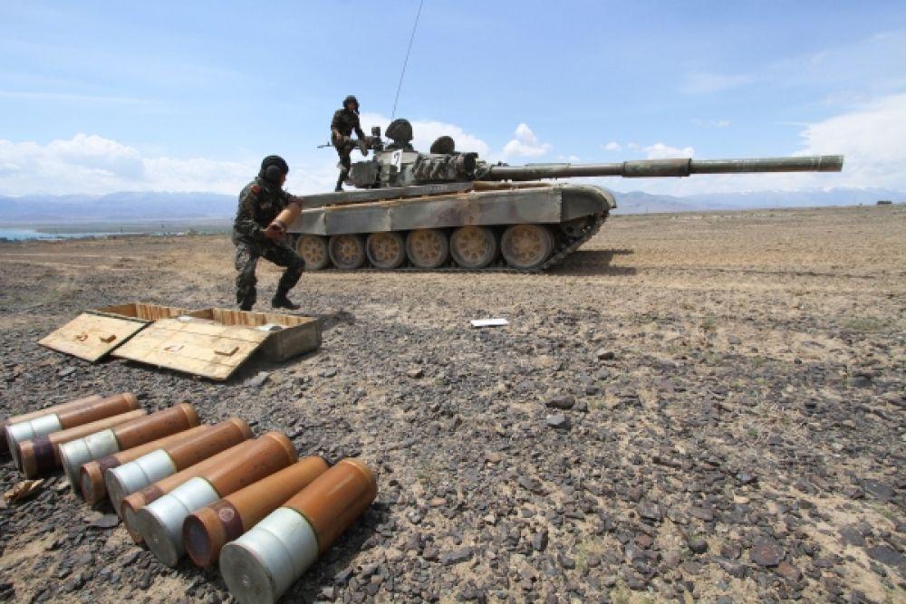 Экипаж танка загружает боеприпасы во время тренировки.