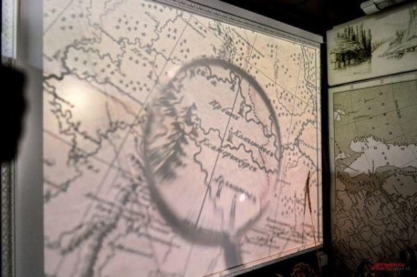 Сквозь лупу на карту в музее смотрит император.