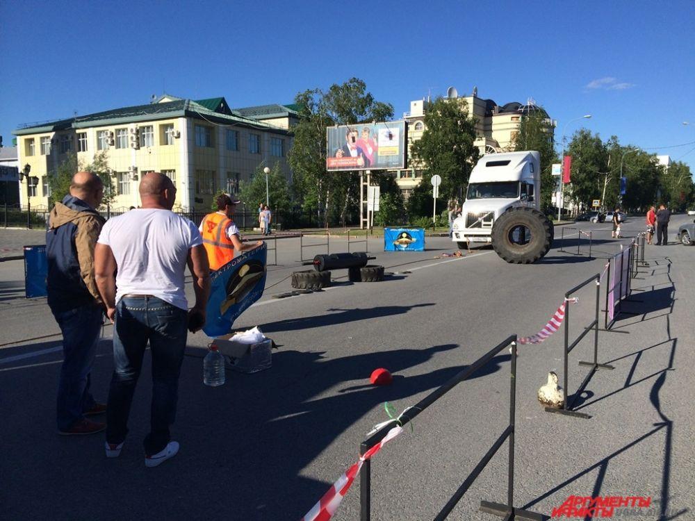 На дороге между парком и КТЦ Югра-Классик силачи готовились к соревнованиям. Им предстояло поднять многокилограммовые колеса и сдвинуть с места грузовик.