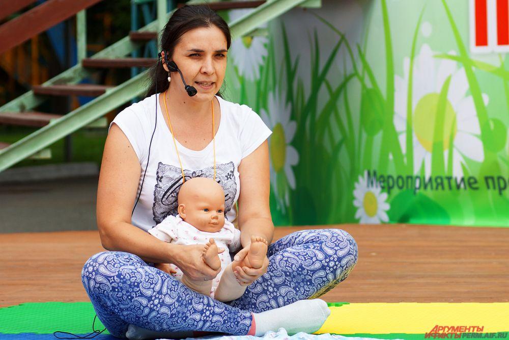 Инструктор по бэби-йоге показывала движения на кукле малыша.