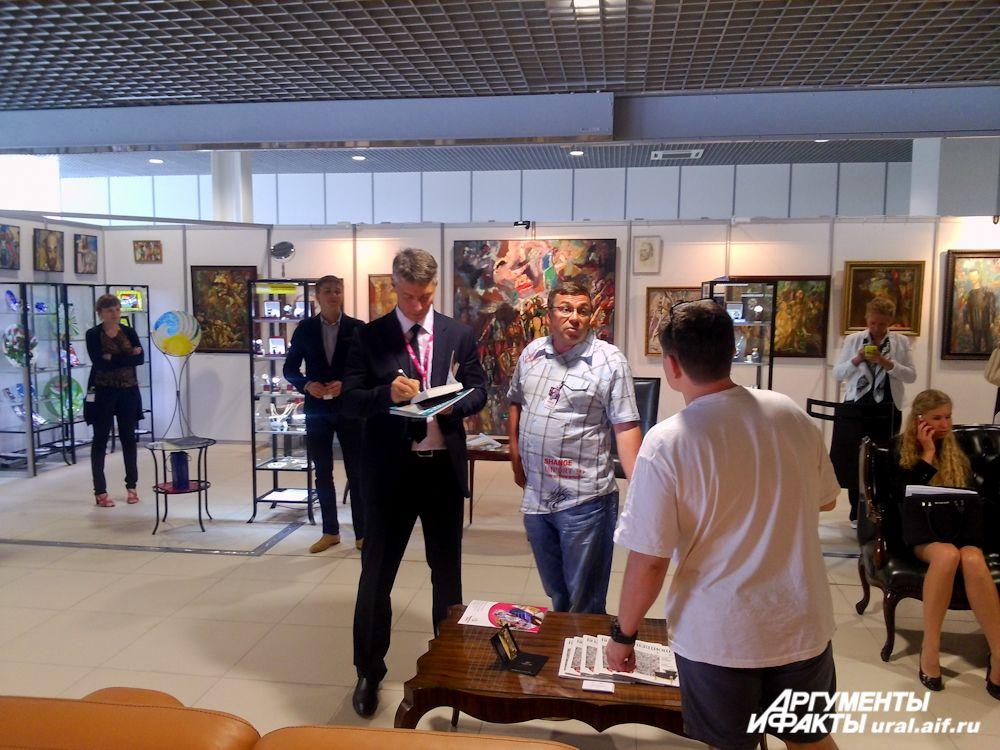 Глава Екатеринбурга Евгений Ройзман на выставке художника Миши Брусиловского. Подписывает читателю свою новую книгу.