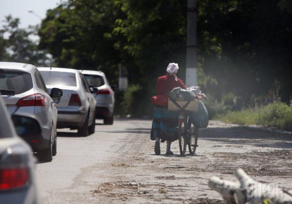 Женщина везет велосипед недалеко от блокпоста