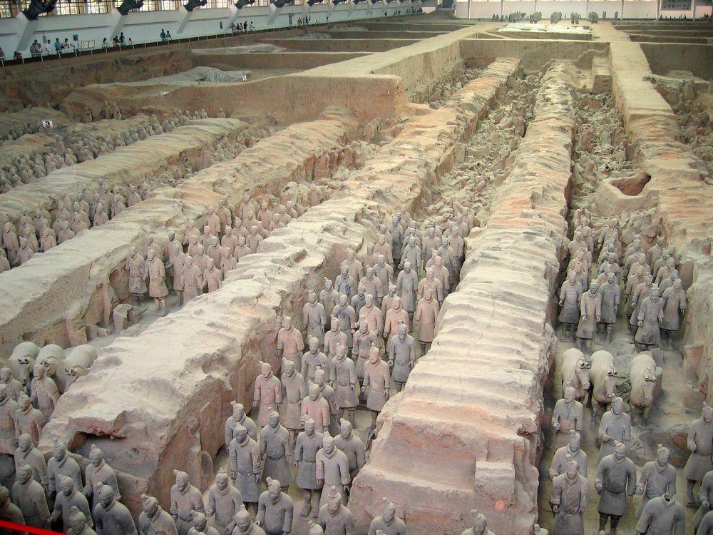 Лагерь терракотовых воинов, находящийся в 1,5 км от гробницы императора, вероятно, должен был удовлетворять властные амбиции Цинь Шихуанди в потустороннем мире. Правитель требовал похоронить с собой 4 тысячи молодых воинов, как того требовала древняя китайская традиция, но приближенные императора убедили его во избежание бунта не делать этого. Так возникла идея создания глиняных копий воинов.