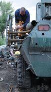 Работник ремонтной бригады при монтаже противокумулятивных решеток на бронетранспортер