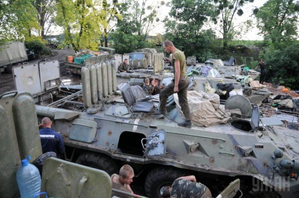 Рабочие сводной ремонтной бригады одного из базовых лагерей АТО ремонтируют бронетранспортеры