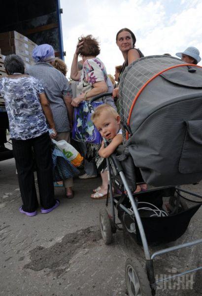 В длинной очереди есть и мамы с малышами
