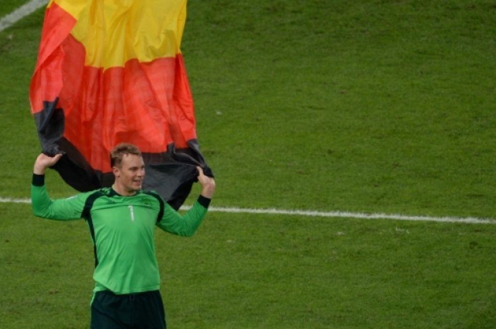Вратарь сборной Германии Мануэль Нойер в немецким флагом празднует победу на чемпионате мира по футболу–2014