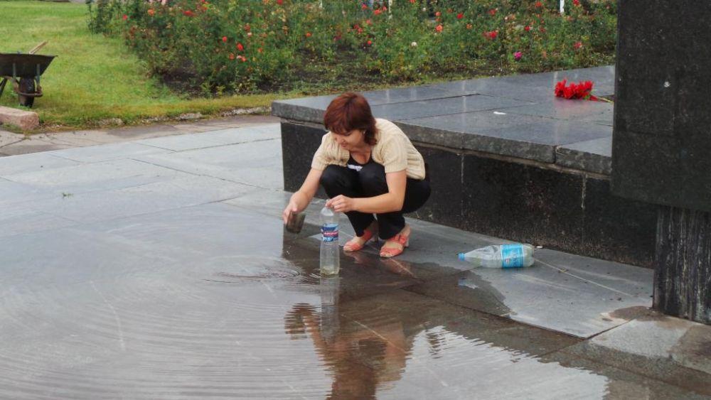Женщина набирает дождевую воду в пластиковую бутылку