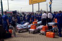 Работники «Скорой помощи» и МЧС готовят носилки для перевозки пострадавших.