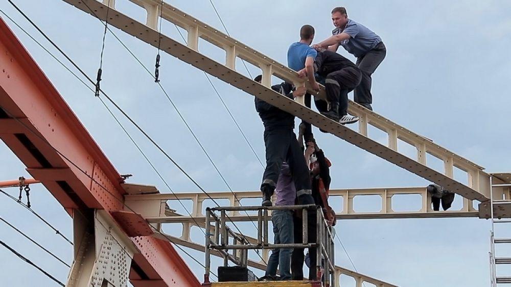 Спасатели осторожно подхватили доведённого до отчаяния молодого человека и передали сотрудникам полиции.