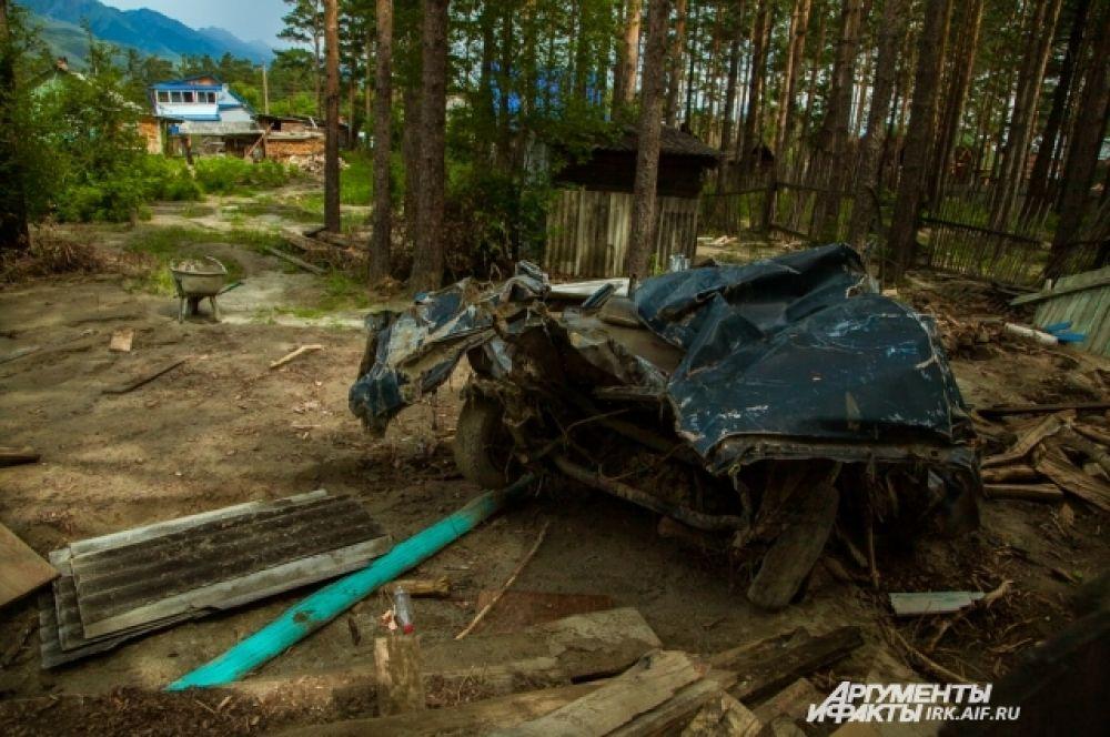 Такую картину можно увидеть на улочках в глубине поселка. Не убраны останки автомобилей.