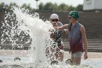 Жители Москвы спасаются от жары у фонтана на Поклонной горе.