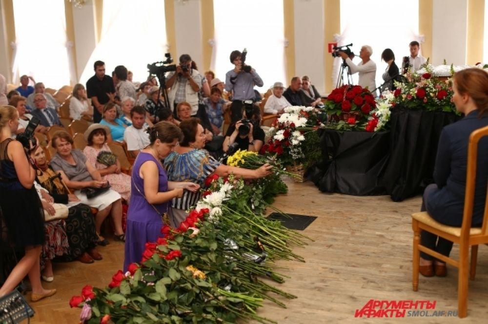 Сцена была усыпана цветами, которые принесли с собой пришедшие на панихиду.
