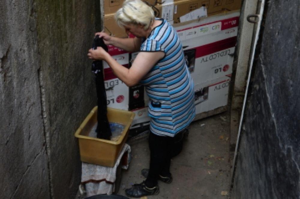 Женщина стирает белье перед входом в подвал жилого дома, где люди вынуждены прятаться от обстрелов.