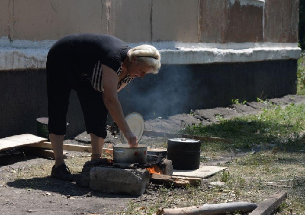 Жительница Шахтерска, лишившаяся дома, готовит еду рядом с подвальным убежищем.