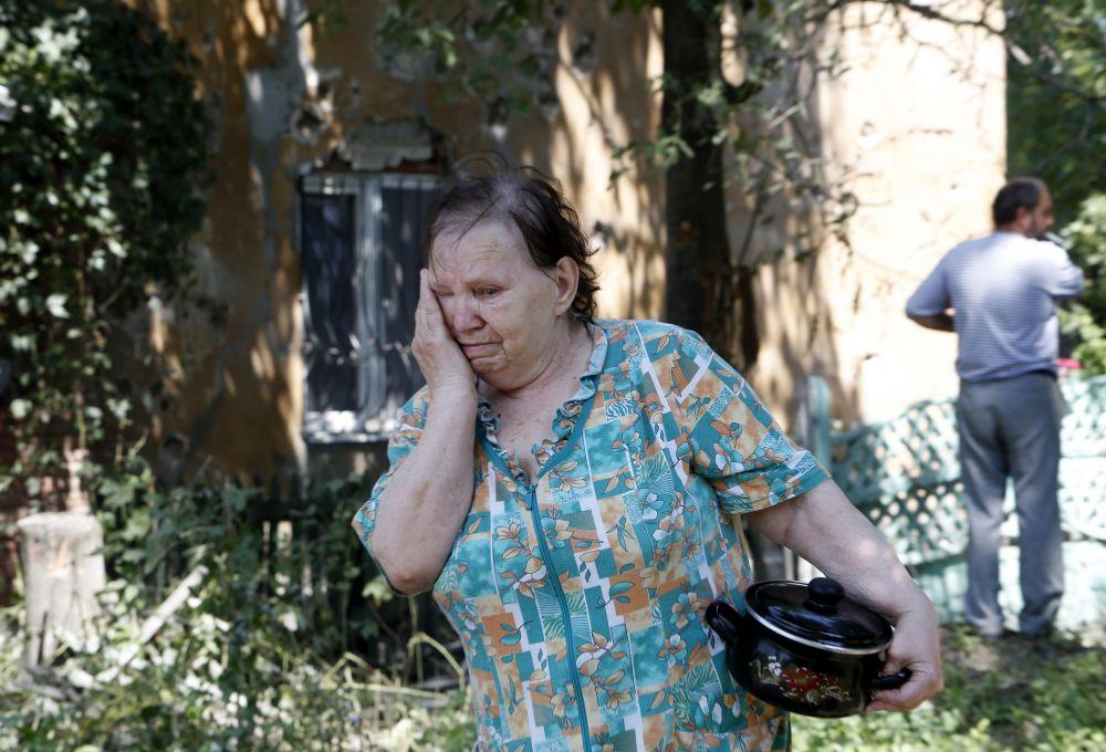 Жительница Донецка проходит мимо обстрелянного 3 августа 2014 года здания, около которого были убиты 9 гражданских лиц.