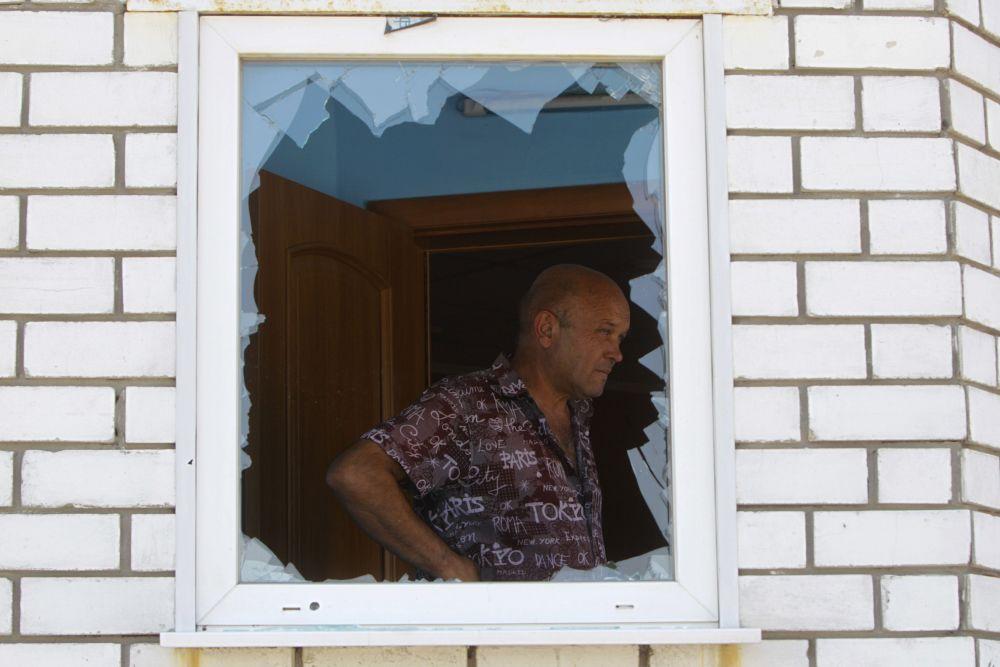 Житель Донецка осматривает здание, где располагалось его кафе, после боя между украинской армией и ополченцами 2 августа 2014 года.