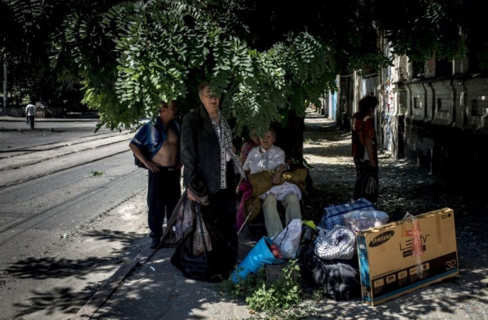 Местные жители Луганска сидят возле своего дома, разрушенного в ходе боев.
