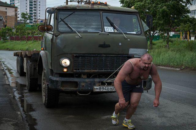 Иван Савкин тянет грузовик.