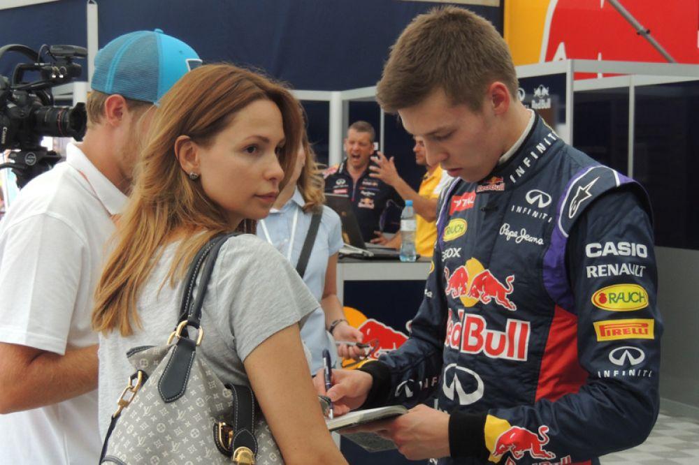 Звезда команды «Формулы-1», российский пилот Даниил Квят раздает автографы.