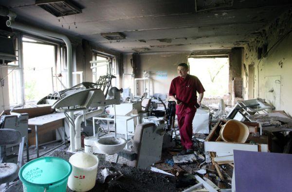 Врач осматривает разрушенную больницу в Донецке