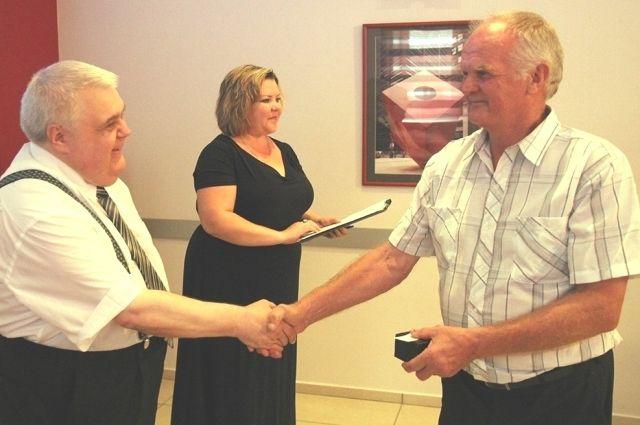 Гендиректор М. Ведерин вручает ценные подарки ветеранам предприятия.